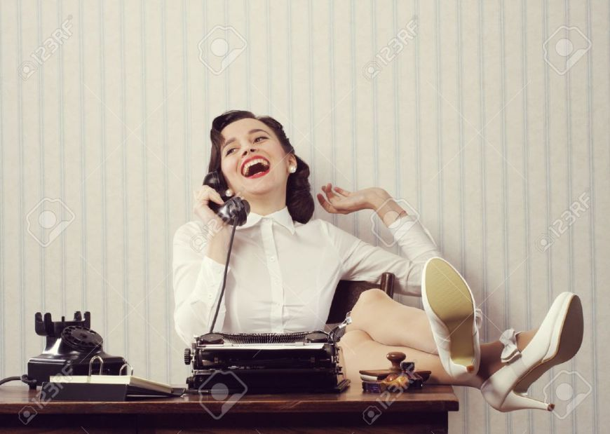 21510658-Cheerful-woman-talking-on-phone-at-desk-Stock-Photo-typewriter